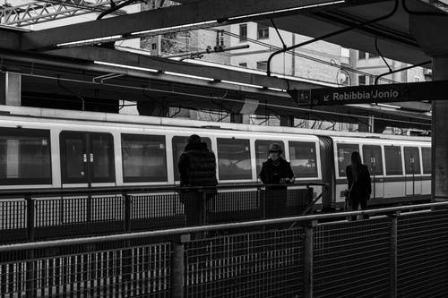Black and white of citizens on railway station walking on platform near public train against modern buildings in city center