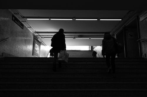 Back view black and white of anonymous passengers walking up staircase leaving subway station