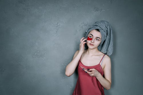 A Woman Putting on a Facial Cream After Bathing