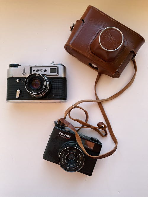 Top view of various analog photo camera with leather case composed together on white table