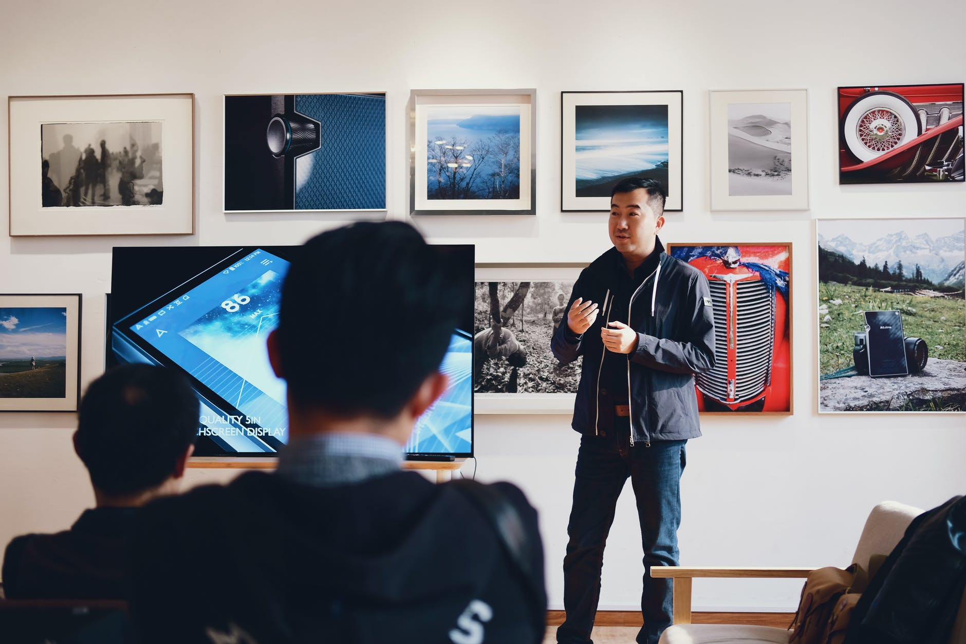 A MAN TALKING TO TWO PEOPLE BESIDE A FLAT SCREEN WITH PHOTOS IN THE BACKGROUND