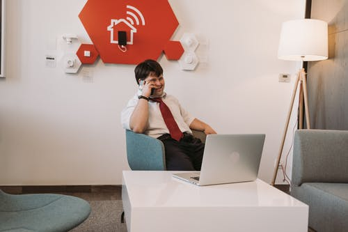 Man Sitting on Chair while Having a Phone Call