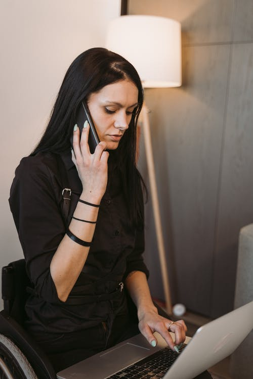 Woman in Black Shirt Holding a Smartphone while Typing on her Laptop