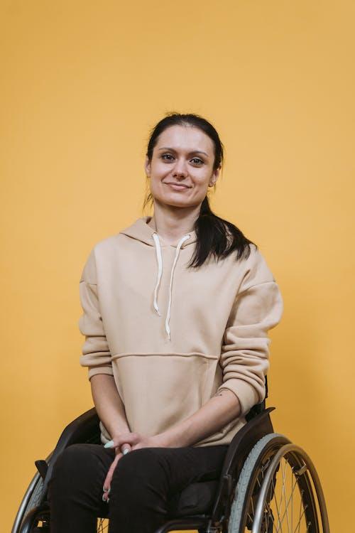 Gratis arkivbilde med brun jakke, funksjonshemmet, gul bakgrunn