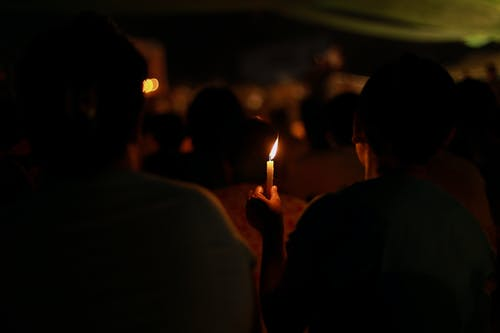 Person Holding a Candlelight in a Dark Night