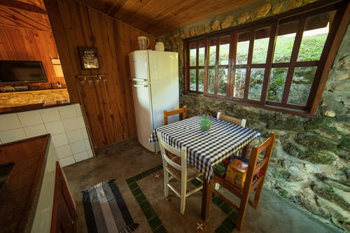 Chairs at table placed near refrigerator at stone wall with window in rural style kitchen with decoration on wooden wall