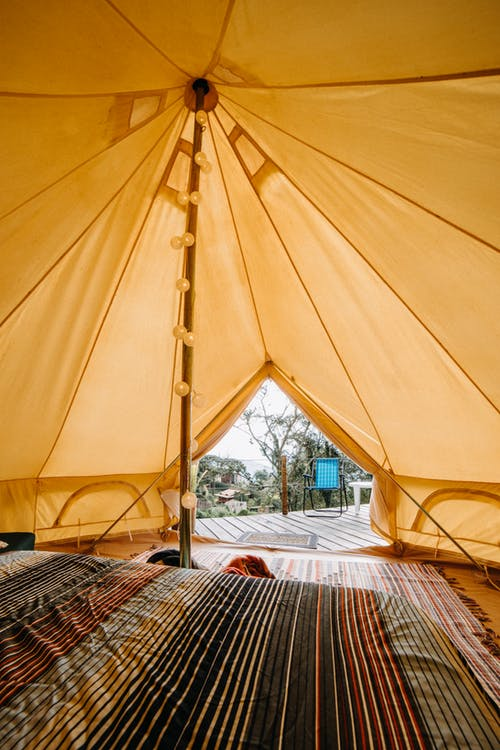Soft bed with colorful blanket placed near bright carpet in tent with yellow roof located in suburb area of countryside