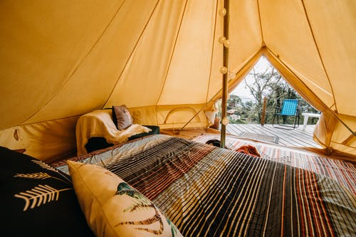 Soft bed with colorful blanket and cushions placed in tent with decorated pole and doorway in rural area of countryside