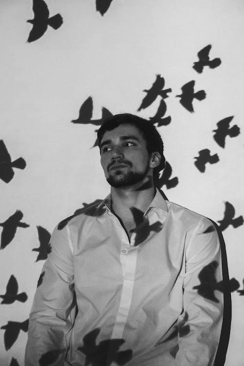Thoughtful man near wall with birds shadows