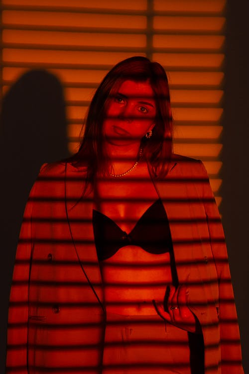 Serious female wearing jacket and bra while looking at camera in dark room with shadows from jalousie