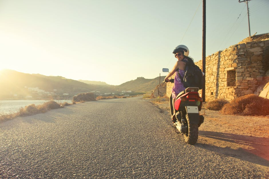 Woman Riding Motor Scooter Travelling on Asphalt Road during Sunrise