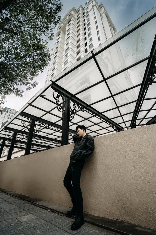 Trendy Asian man near metal structure on street