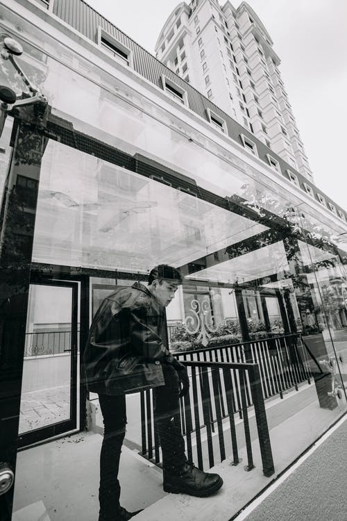 Through glass of Asian man standing on bus stop