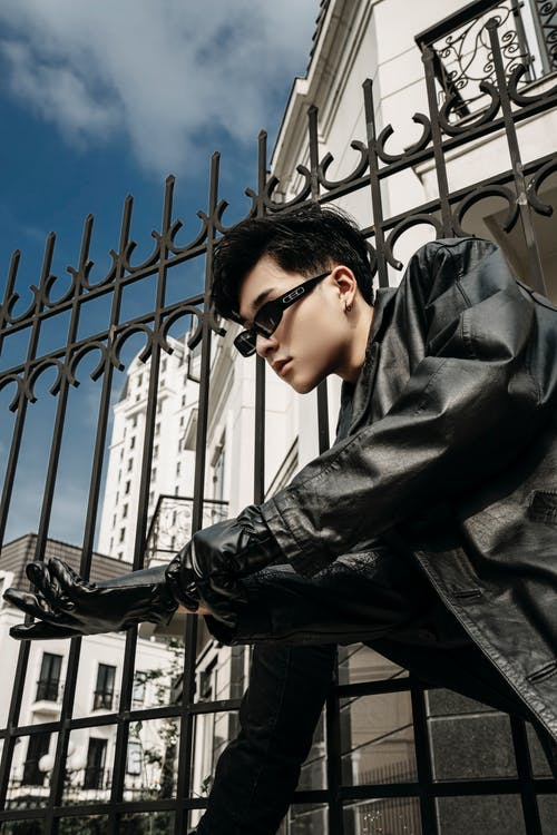 Low angle side view of trendy ethnic man in leather jacket putting on glove against urban houses