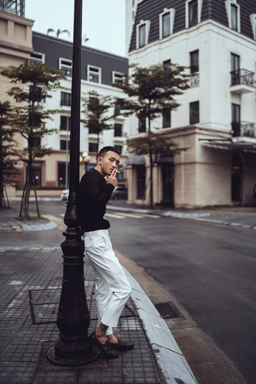 Side view of self assured young ethnic guy in trendy outfit smoking cigarette and looking at camera while leaning on pillar on city street