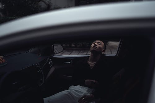 Through window of relaxed young Asian guy in casual clothes lying in modern car with closed eyes in evening