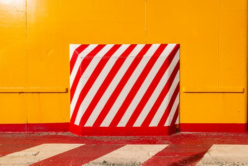 Red White and Blue Striped Flag on Yellow Wall