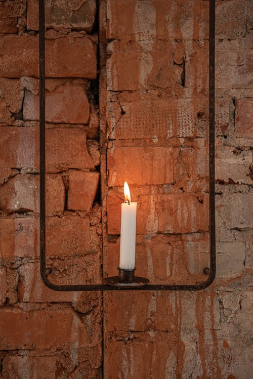 White Candle on Brown Metal Holder