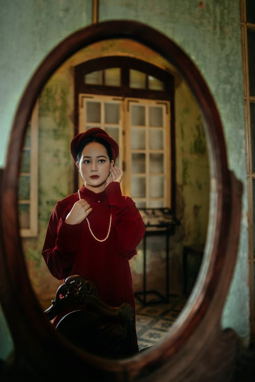 Emotionless Asian woman looking in oval mirror
