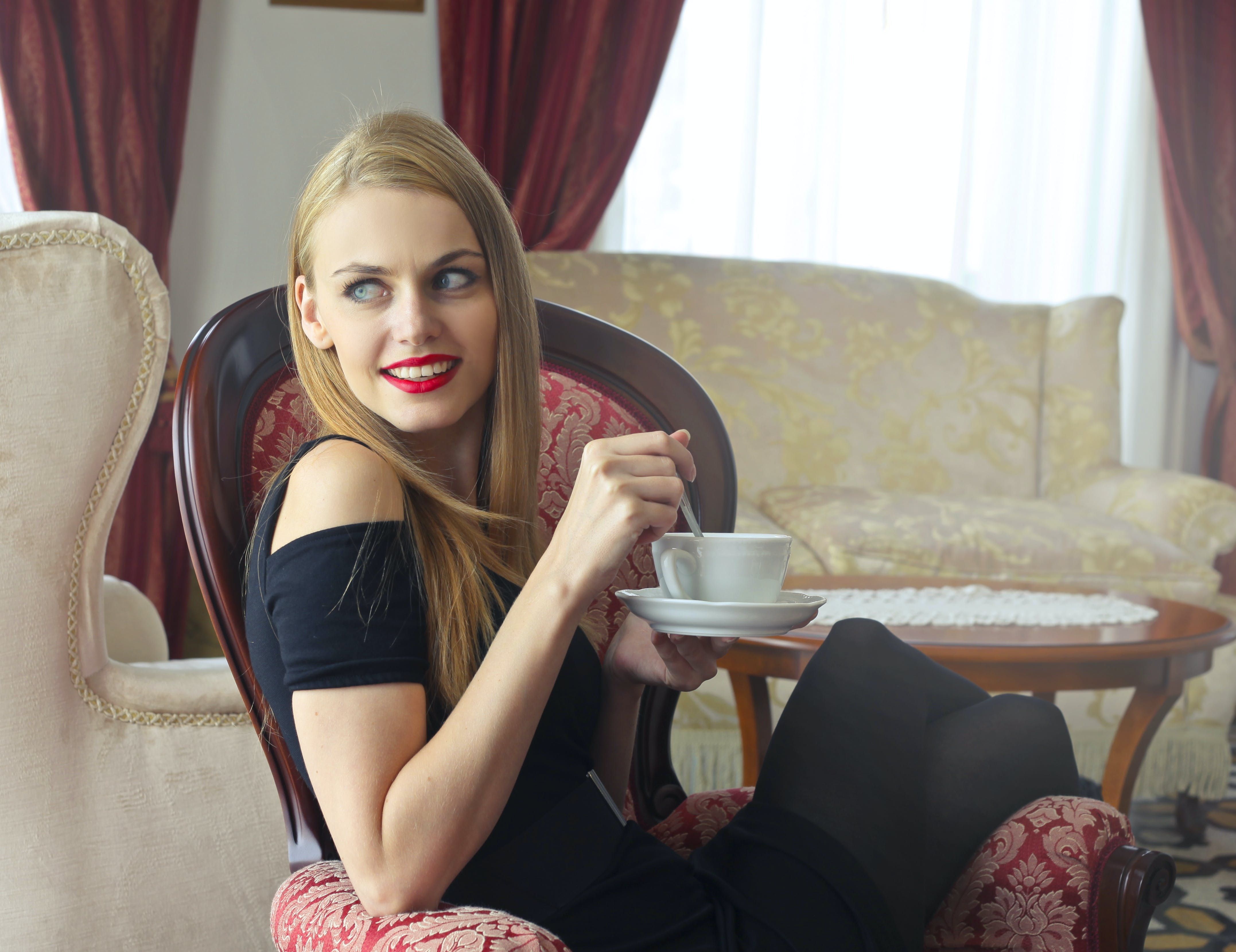 Woman in Black Cold-shoulder Dress Holding Tea Cup With Saucer