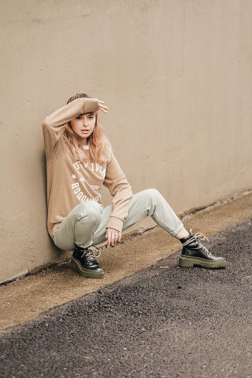 Woman in Beige Long Sleeve Shirt and White Pants Sitting on Gray Concrete Floor