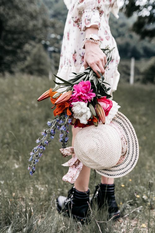 Back view of crop unrecognizable female in dress with hat and blossoming flowers standing on meadow