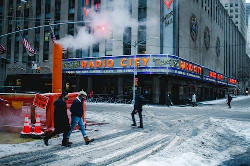 Anonymous people walking in snowy city during coronavirus pandemic