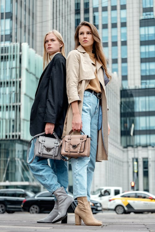 Woman in Black Coat and Blue Denim Jeans With Brown Leather Sling Bag
