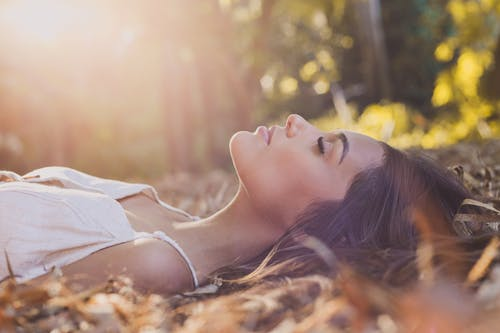 Woman in White Dress Lying on Brown Dried Leaves
