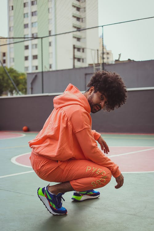 Woman in Orange Hoodie and Brown Pants Sitting on Basketball Court