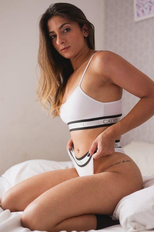 Woman in White and Black Bikini on Bed