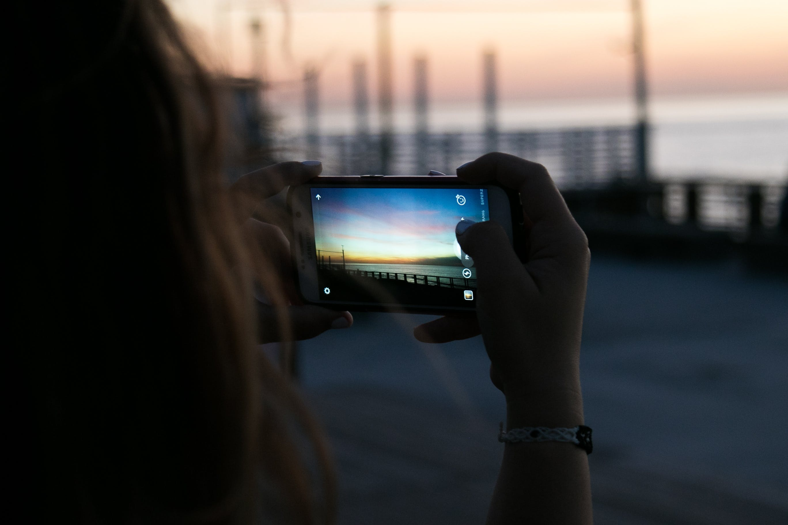 Brown Haired Woman Taking a Photo of Sunset