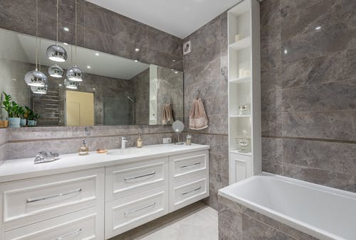 Interior of contemporary bathroom with white furniture and bathtub