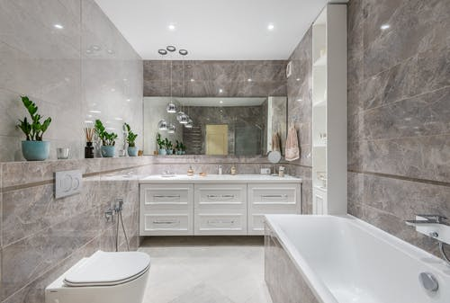 Spacious bathroom with bathtub and mirror hanging over white cupboard
