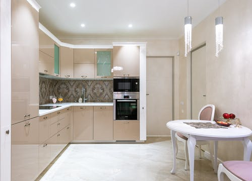 Interior of light kitchen with glossy furniture and built in appliances