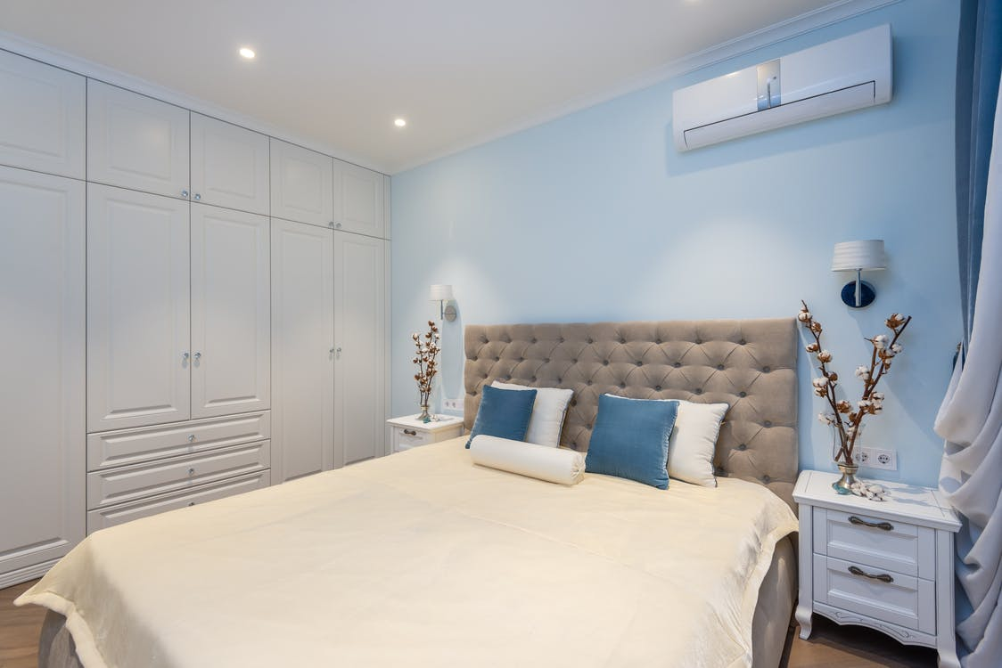 Comfortable bed and white big wardrobe in elegant bedroom