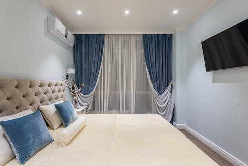 Interior of cozy bedroom with soft bed and blue cushions and curtains
