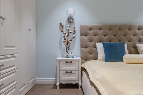 White classic styled wardrobe and nightstand decorated with vase with cotton plants placed near comfortable bed with cushions in cozy apartment
