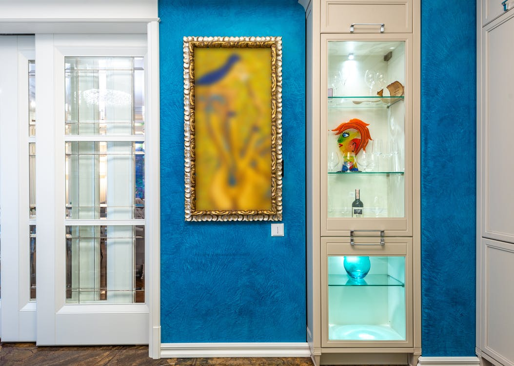 Blue Wall Behind the Glassware Cabinet in a Brightly Lit Room