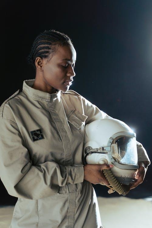 A Female Astronaut Holding a Helmet