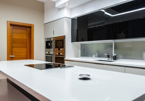 Interior of modern spacious kitchen area with minimalistic style placed in contemporary apartment