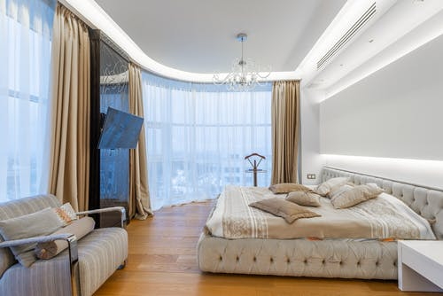 Interior of luxury bedroom with large comfortable bed and stylish furniture in contemporary apartment in daylight