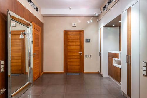 Interior of empty spacious hallway with wooden doors and large mirror in contemporary apartment