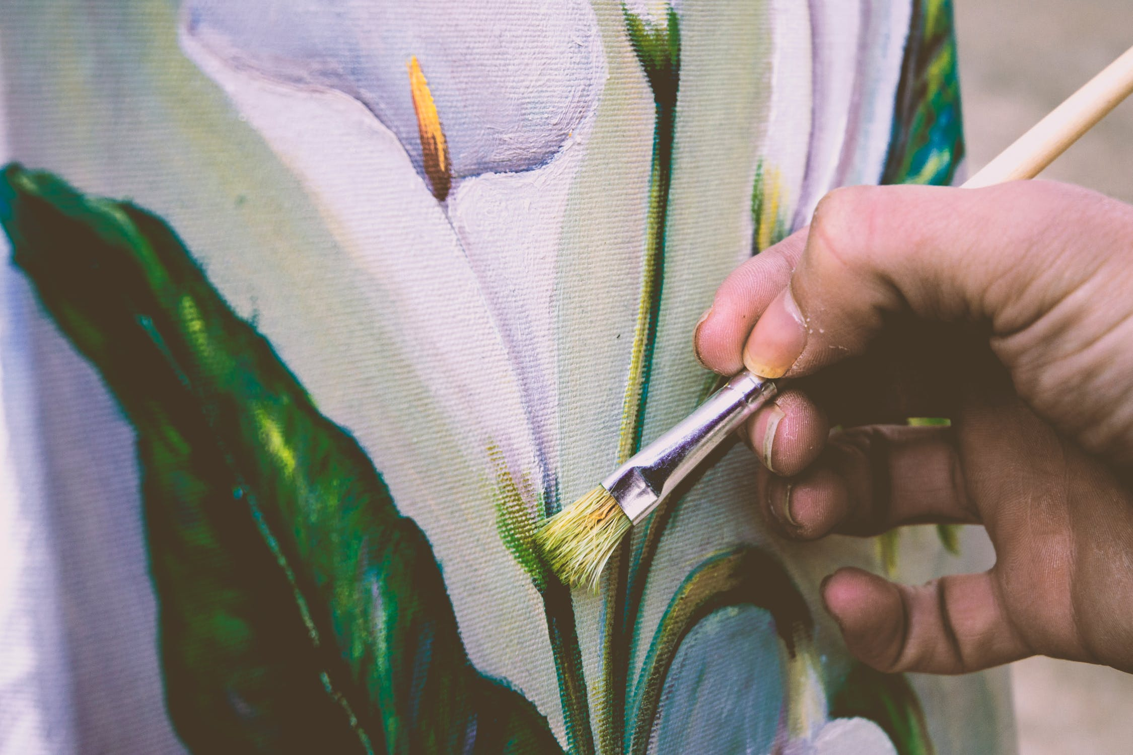 A hand touching up an oil canvas painting of a lily
