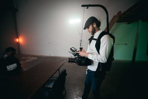 Man in White Shirt and Blue Denim Jeans Holding Black Video Camera