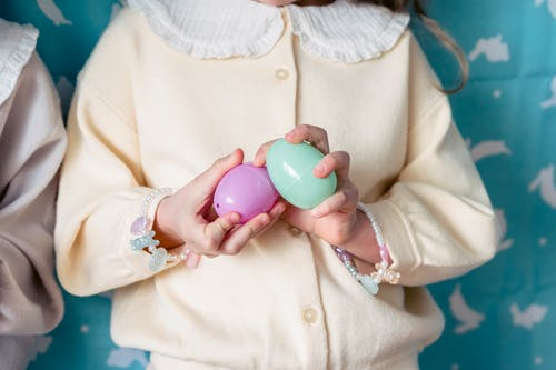 Crop unrecognizable girl in light clothes holding multicolored toy eggs against blue wall in kindergarten