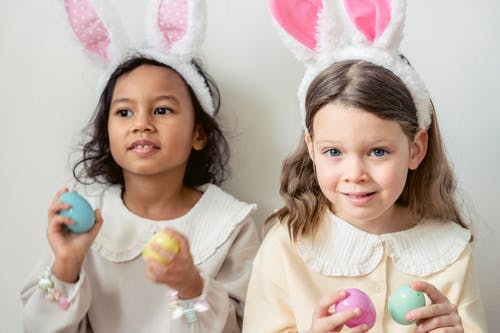 Cute content multiracial girls in light wear and funny bunny ears playing with multicolored toy Easter eggs against white wall