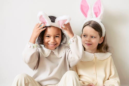 Happy diverse girls wearing bunny ears in kindergarten