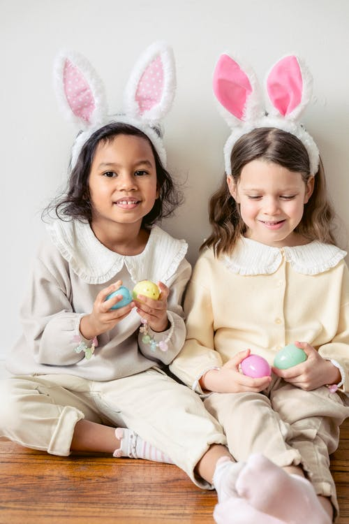 Adorable diverse girls wearing soft light clothes and funny bunny ears sitting on floor together with toy eggs
