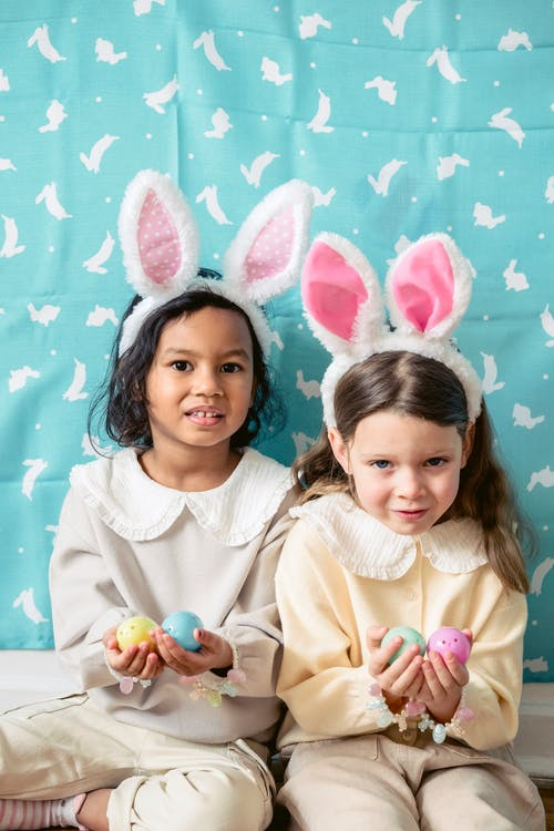 Positive diverse girl in bunny ears playing with Easter eggs